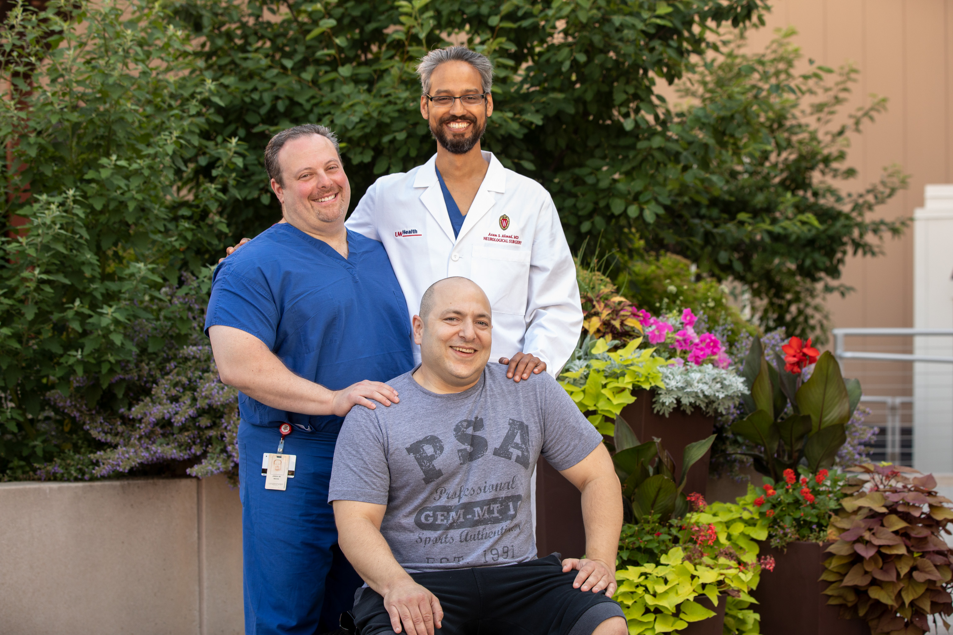 Jordan Dorf (seated) travelled from Denver to Madison to have his pituitary tumor removed by UW Health neurosurgeon Azam Ahmed, MD (standing, right). Jordan learned about Dr. Ahmed from UW Health neurosurgeon Josh Medow, MD (standing, left). Jordan and Dr. Medow have been friends since high school in Skokie, IL.